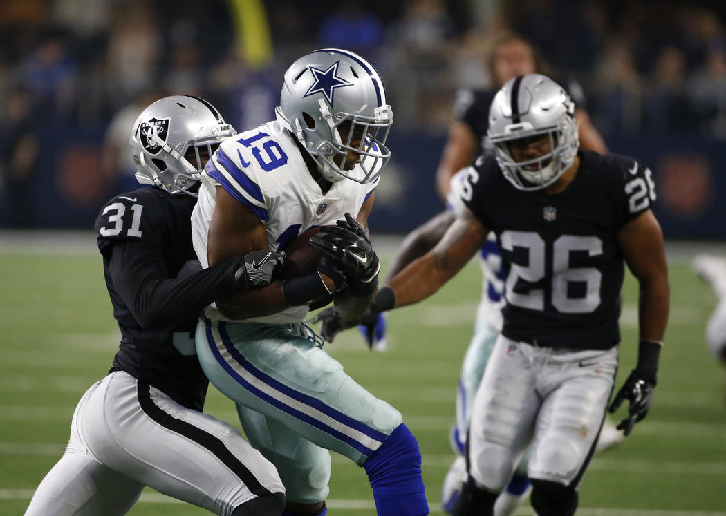 Oakland Raiders' Breon Borders (31) and Shalom Luani (26) stop Dallas Cowboys wide receiver Brice Butler (19) after Butler caught a pass in the second half of a preseason NFL football game, Saturd ...