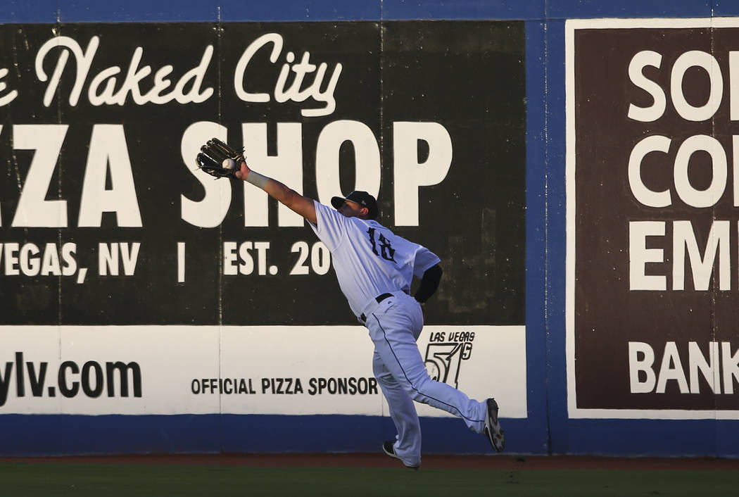 "Las Vegas 51s' Travis Taijeron (18) catches a fly ball from the Colorado Springs Sky Sox during the debut of the ""Reyes de Plata"" (Silver Kings), part of a new Minor League Baseb ..."