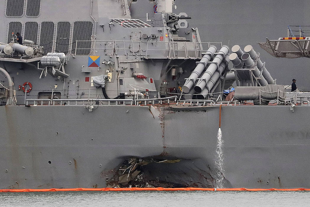 The damaged port aft hull of the USS John S. McCain is visible while docked at Singapore's Changi naval base in Singapore on Aug. 22.  (AP Photo/Wong Maye-E, File)