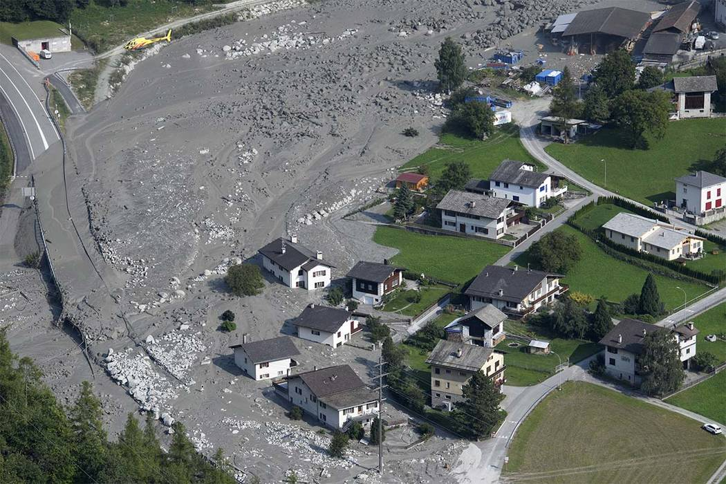 A rocky mudslide rushes toward the village of Bondo, Graubuenden in southern Switzerland, Friday, Aug. 25, 2017, after it was already hit by one on Wednesday. (Gian Ehrenzeller/Keystone via AP)