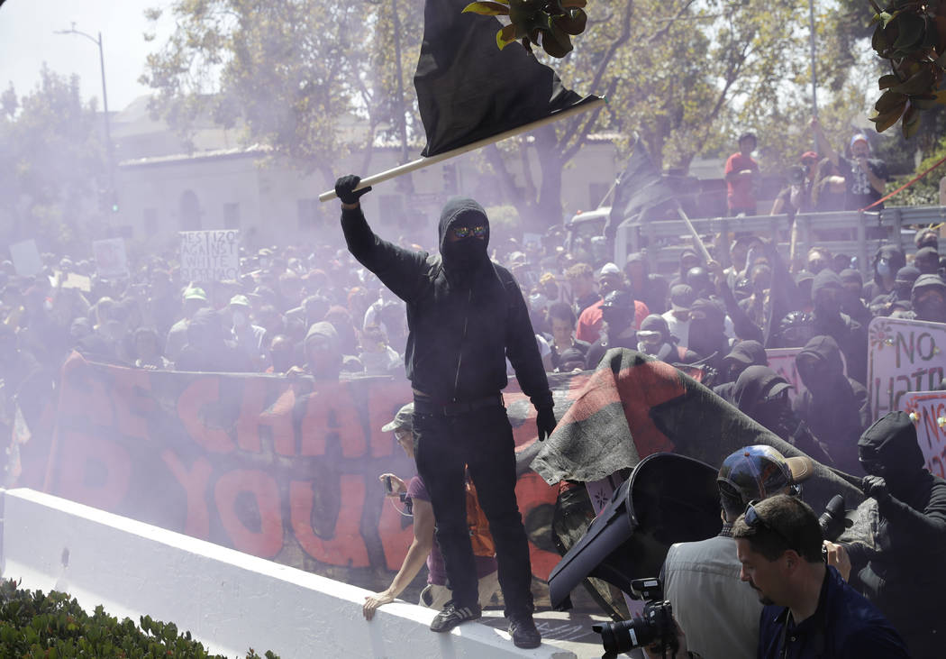 """An anti-fascist demonstrator jumps over a barricade during a free speech rally Sunday, Aug. 27, 2017, in Berkeley, Calif. Several thousand people converged in Berkeley Sunday for a """"Rally ..."""