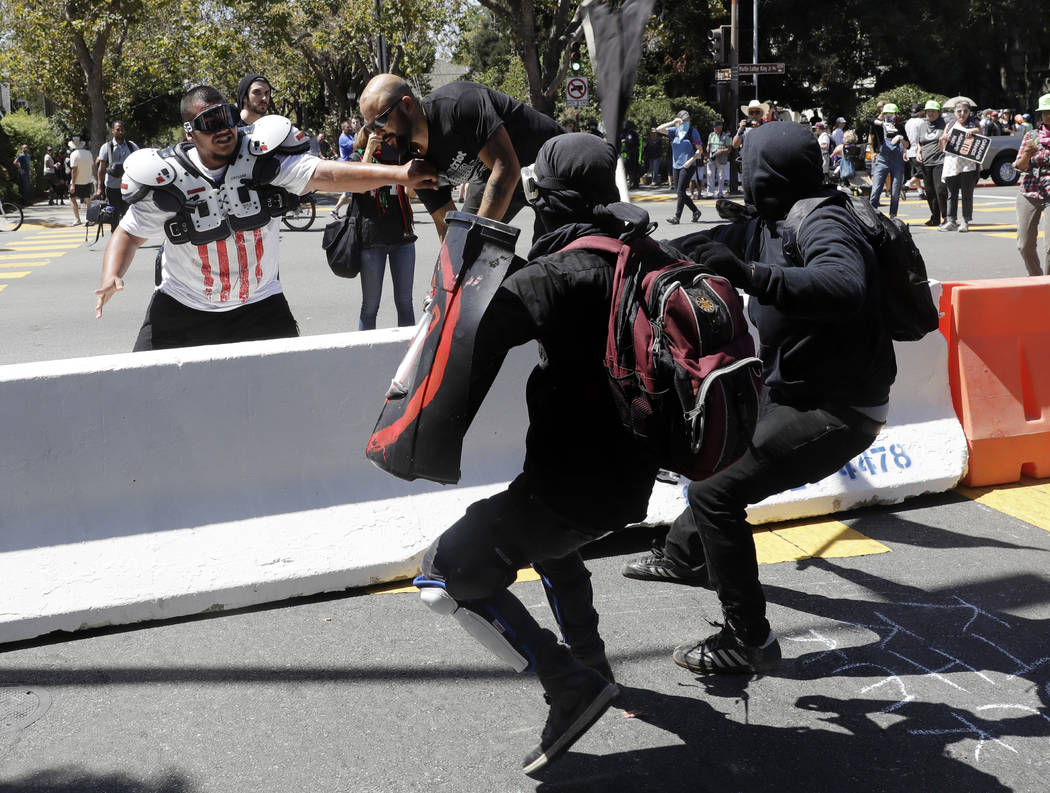 Demonstrator Joey Gibson, second from left, is chased by anti-fascists during a free speech rally Sunday, Aug. 27, 2017, in Berkeley, Calif. Several thousand people converged in Berkeley Sunday fo ...