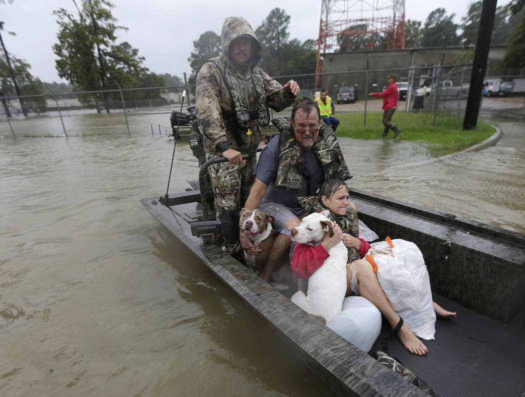 John and Cathy Cservek hold their dogs Lacy and Iggy while being rescued from their home as floodwaters from Tropical Storm Harvey rise Monday, Aug. 28, 2017, in Spring, Texas. (AP Photo/David J.  ...