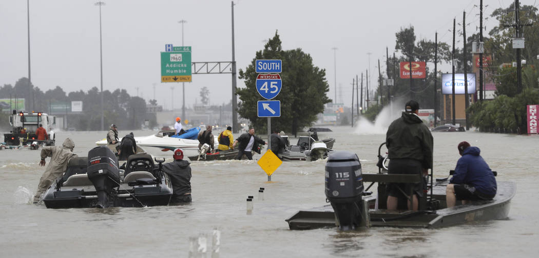 Volunteer rescue boats make their way into a flooded subdivision to rescue stranded residents as floodwaters from Tropical Storm Harvey rise Monday, Aug. 28, 2017, in Spring, Texas. (AP Photo/Davi ...