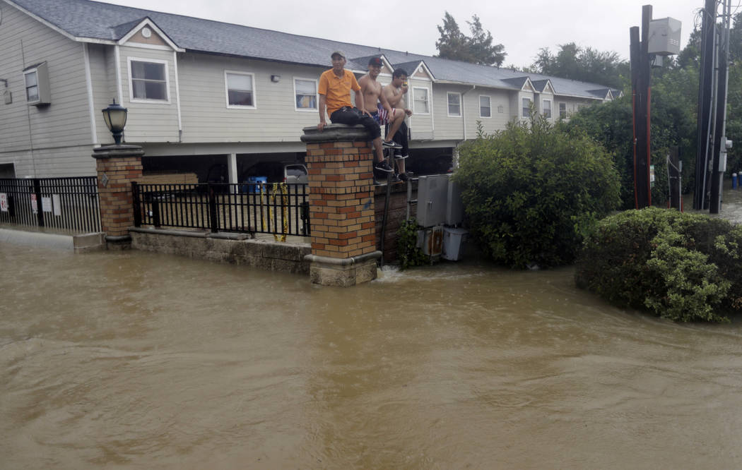 Residents sit on a fence surrounded by floodwaters from Tropical Storm Harvey on Sunday, Aug. 27, 2017, in Houston, Texas. (AP Photo/David J. Phillip)