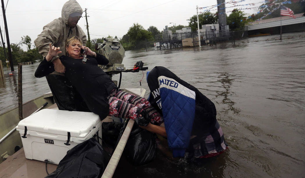 Rhonda Worthington is lifted into a boat while on her cell phone with a 911 dispatcher after her car become stuck in rising floodwaters from Tropical Storm Harvey in Houston, Texas, Monday, Aug. 2 ...