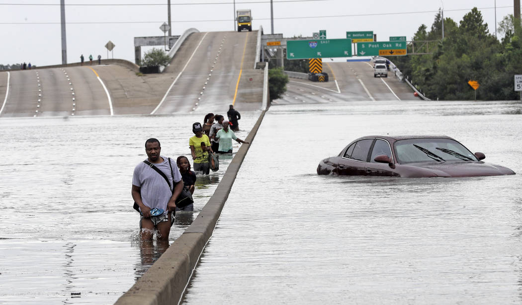 Evacuees wade down a flooded section of Interstate 610 as floodwaters from Tropical Storm Harvey rise Sunday, Aug. 27, 2017, in Houston. The remnants of Hurricane Harvey sent devastating floods po ...