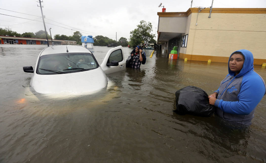 Conception Casa, center, and his friend Jose Martinez, right, check on Rhonda Worthington after her car become stuck in rising floodwaters from Tropical Storm Harvey in Houston, Texas, Monday, Aug ...