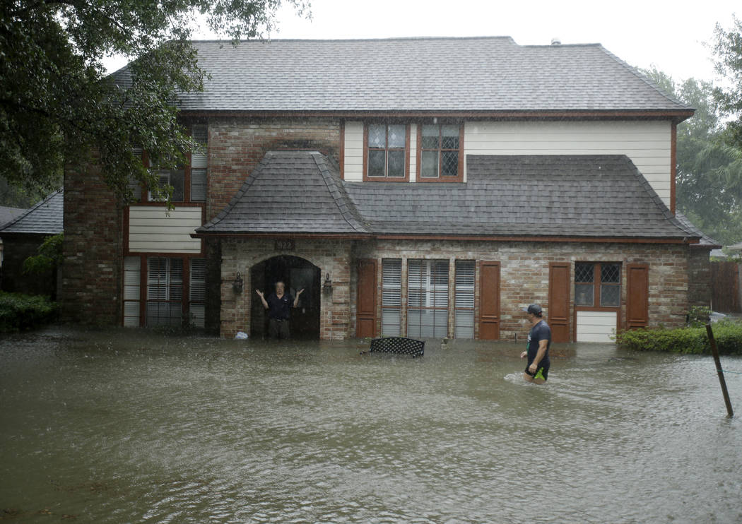 A man standing in the doorway of his flooded home responds to an evacuation offer in a neighborhood inundated by floodwaters from Tropical Storm Harvey on Monday, Aug. 28, 2017, in Houston, Texas. ...