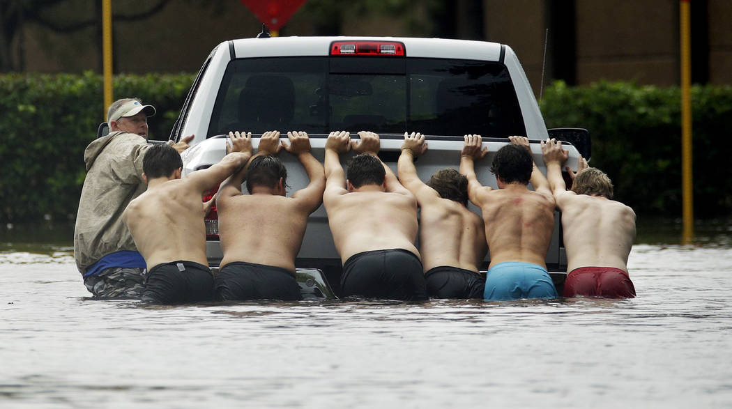 People push a stalled pickup through a flooded street in Houston, after Tropical Storm Harvey dumped heavy rains, Sunday, Aug. 27, 2017. The remnants of Harvey sent devastating floods pouring into ...