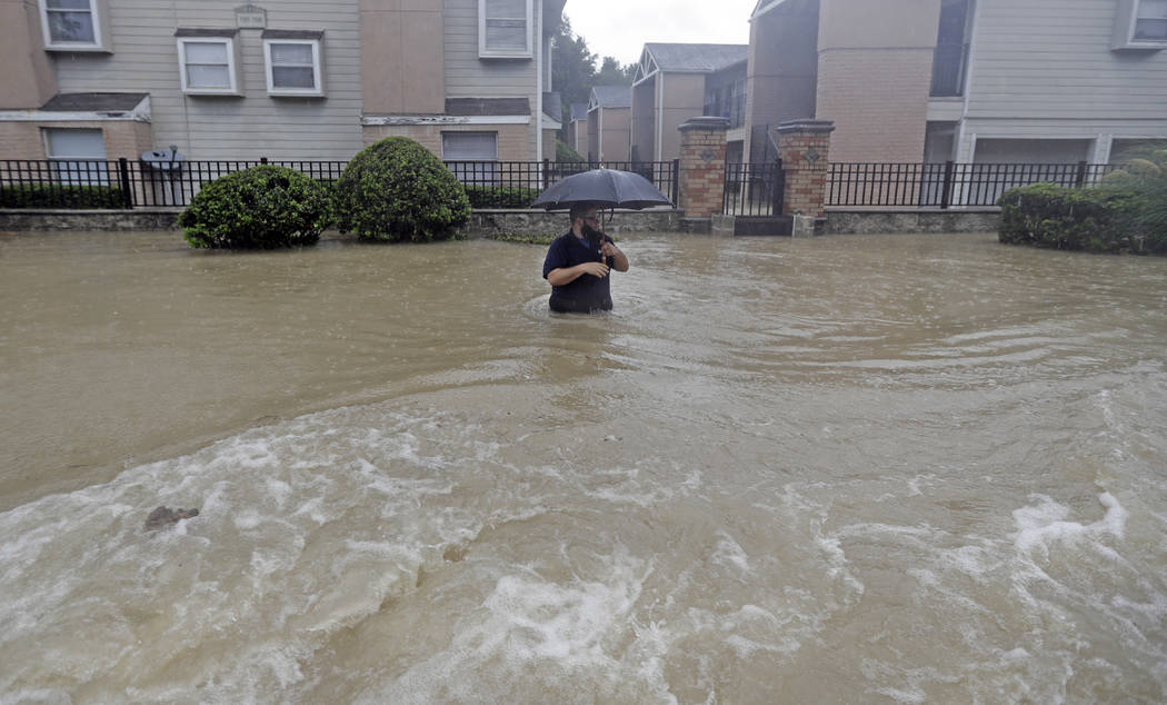 A man wades through floodwaters from Tropical Storm Harvey on Sunday, Aug. 27, 2017, in Houston, Texas. (AP Photo/David J. Phillip)
