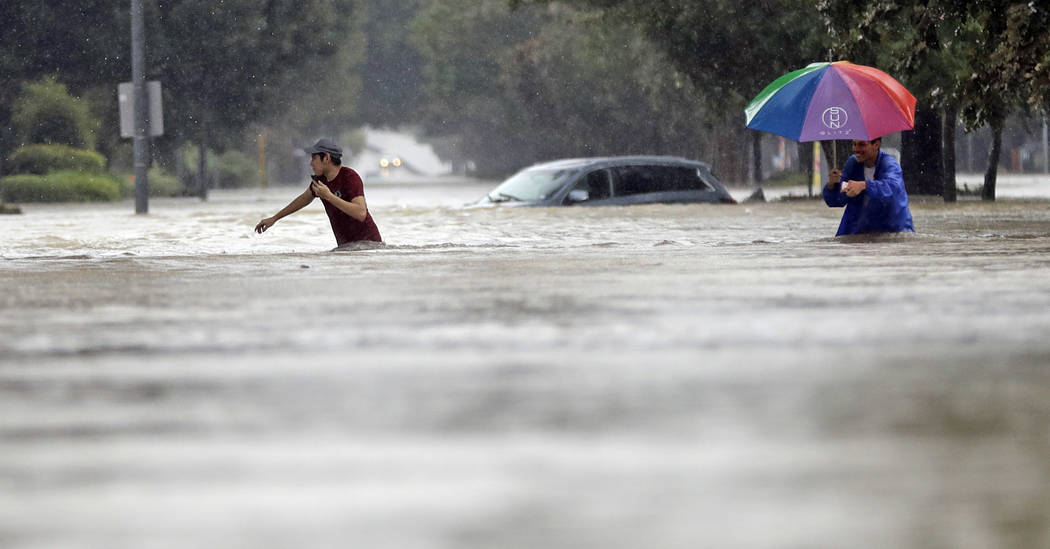Moses Juarez, left, and Anselmo Padilla wade through floodwaters from Tropical Storm Harvey on Sunday, Aug. 27, 2017, in Houston, Texas. (AP Photo/David J. Phillip)