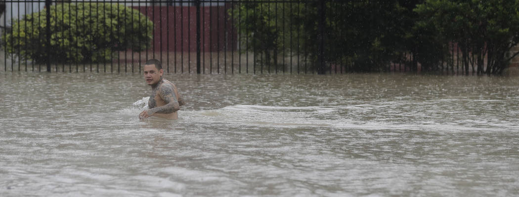 A man wades through floodwaters from Tropical Storm Harvey Sunday, Aug. 27, 2017, in Houston, Texas. (AP Photo/David J. Phillip)