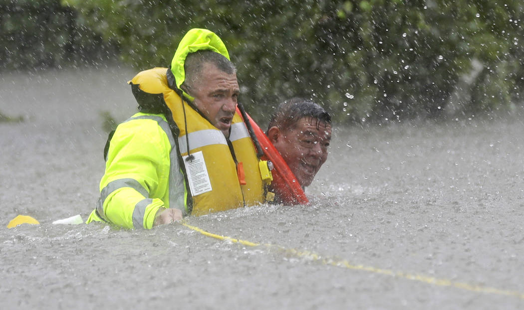 Wilford Martinez, right, is rescued from his flooded car by Harris County Sheriff's Department Richard Wagner along Interstate 610 in floodwaters from Tropical Storm Harvey on Sunday, Aug. 27, 201 ...