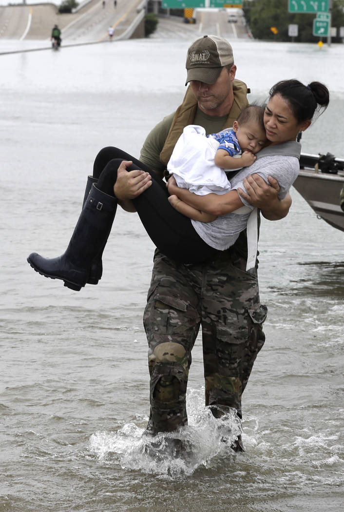 Houston Police SWAT officer Daryl Hudeck carries Catherine Pham and her 13-month-old son Aiden after rescuing them from their home surrounded by floodwaters from Tropical Storm Harvey Sunday, Aug. ...