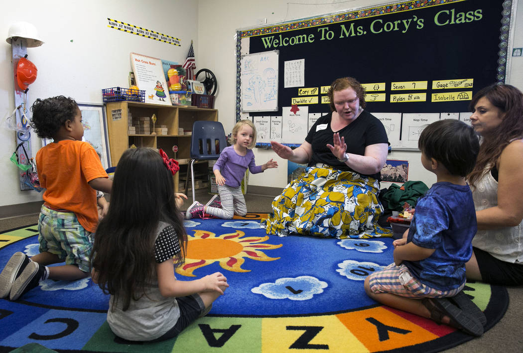 Charlotte Spilman, center, Gage Cummings, left, Rylan Standart, Tommy McGovern, right, and their pre-K teacher Corrine Rocha listen to Melissa Richardson, master teacher teaching artist from Wolf  ...