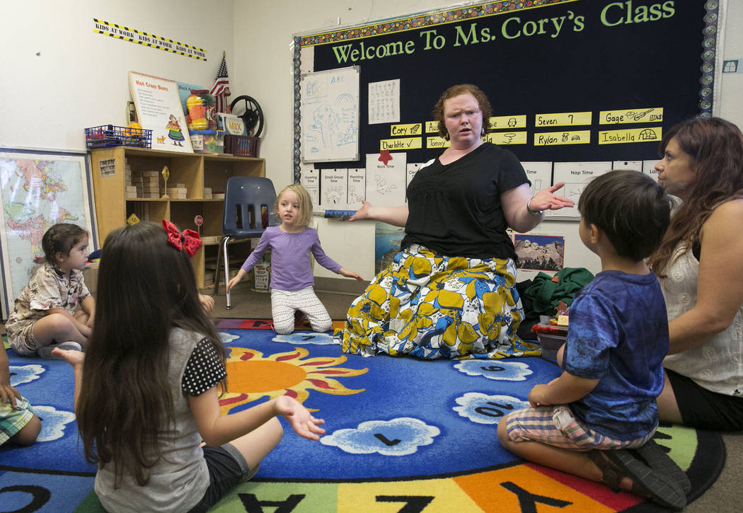 Charlotte Spilman, center, Isabella Saucedo, left, Rylan Standart, Tommy McGovern, right, and their pre-K teacher Corrine Rocha listen to Melissa Richardson, master teacher teaching artist from Wo ...