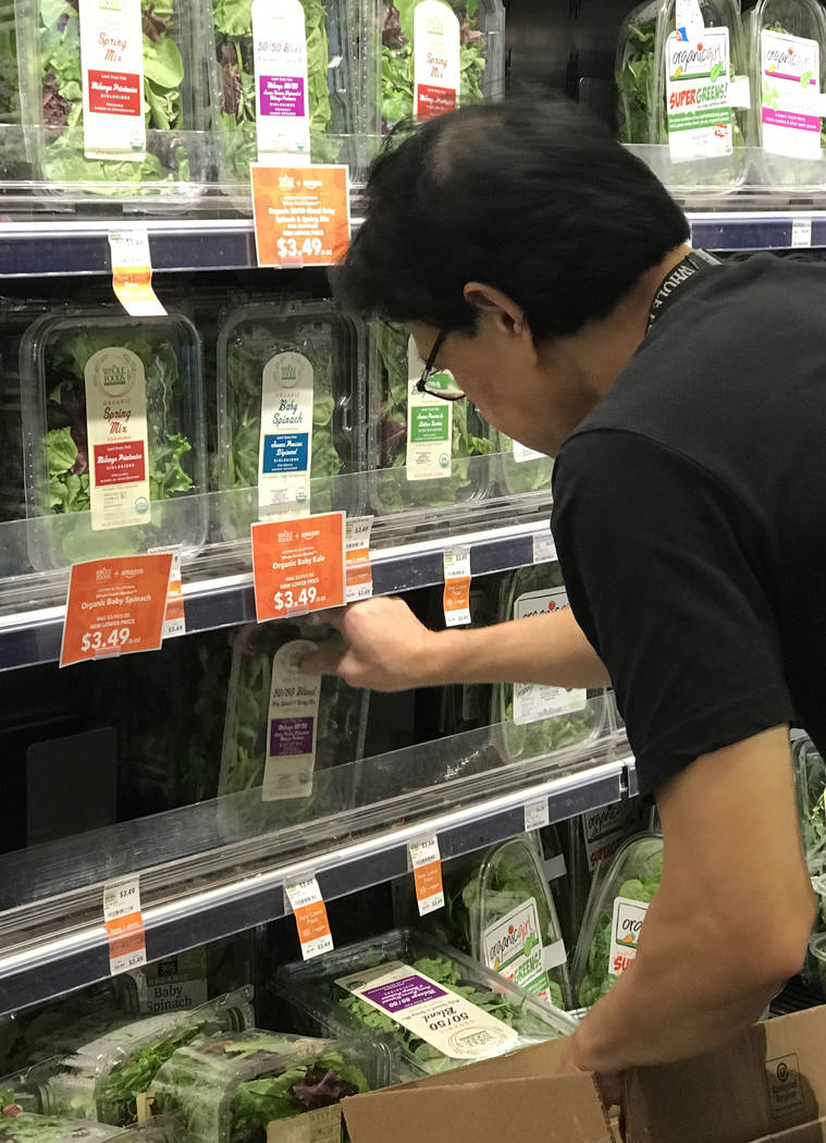 A store associate stocks produce at the Summerlin Whole Foods Market on Monday, Aug. 28, 2017, in Las Vegas. Amazon kicked off its first day as the owner of Whole Foods by slashing prices and addi ...