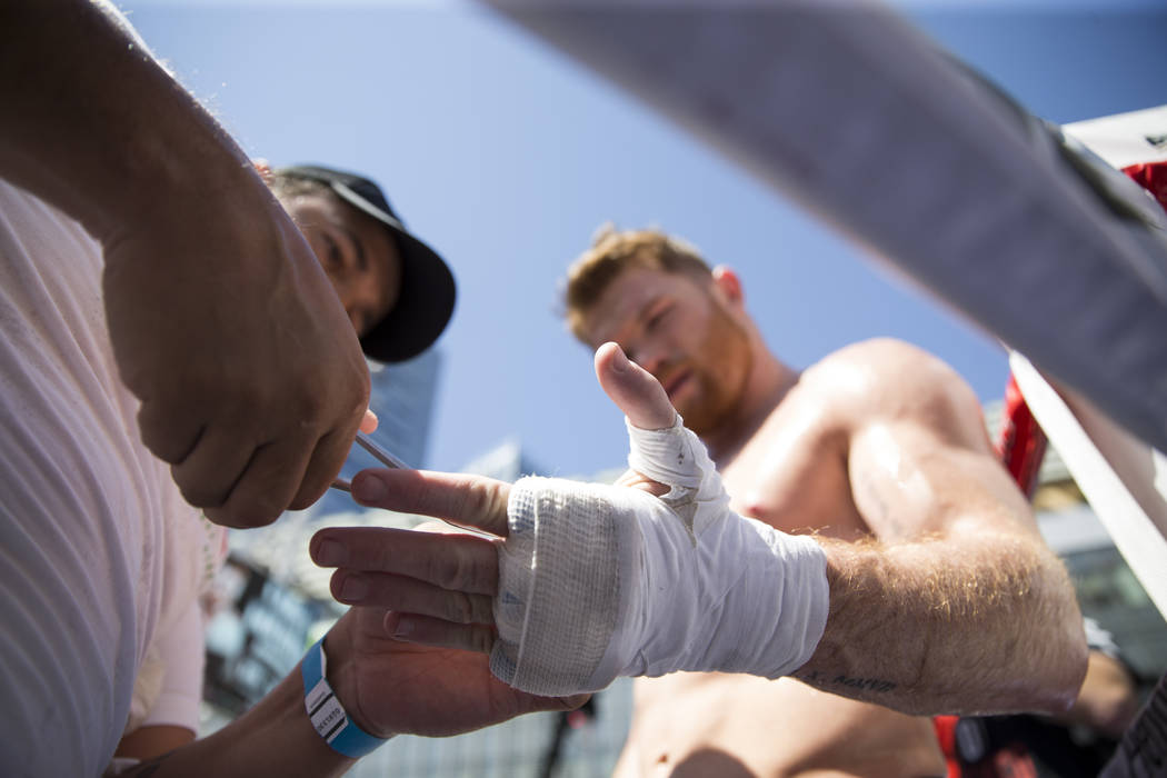 "Saul ""Canelo"" Alvarez, right, gets his hands wraps removed by his trainer Eddy Reynoso during a media workout at L.A. Live in Los Angeles, Calif., on Monday, Aug. 28, 2017. Erik  ..."