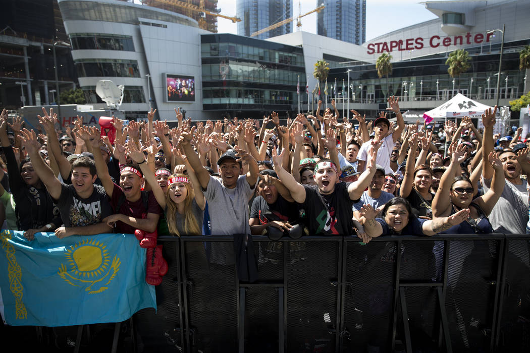 "Fans raise their arms to receive promotional merchandise during a media workout event for Saul ""Canelo"" Alvarez and Gennady Golovkin at L.A. Live in Los Angeles, Calif., on Monda ..."