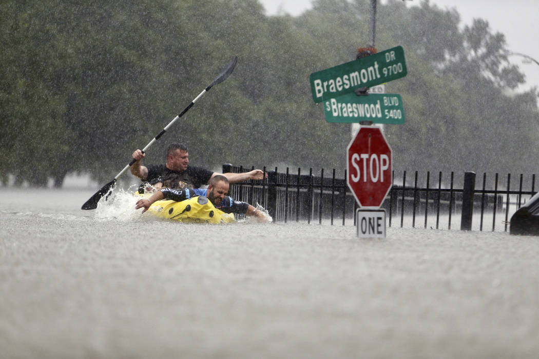 Two kayakers try to beat the current pushing them down an overflowing Brays Bayou along S. Braeswood in Houston, Texas, Sunday, Aug. 27, 2017. Rescuers answered hundreds of calls for help Sunday a ...