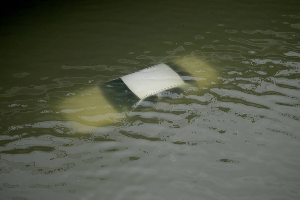 A car is submerged on a freeway flooded by Tropical Storm Harvey on Sunday, Aug. 27, 2017, near downtown Houston, Texas. The remnants of Hurricane Harvey sent devastating floods pouring into Houst ...