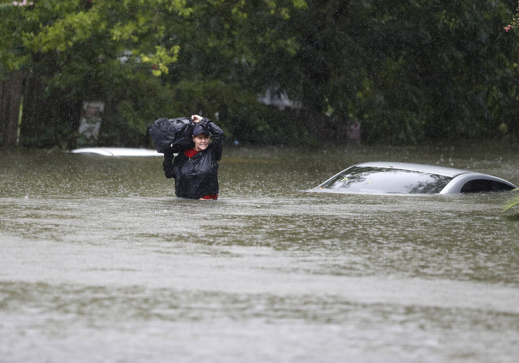 Women carry belongings from an apartment under water on Houston Avenue near Woodland Park after heavy rain from Hurricane Harvey fell overnight, Sunday, Aug. 27, 2017, in Houston. The remnants of  ...