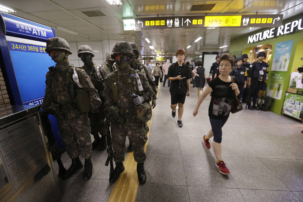 Passengers walk past army soldiers Tuesday, Aug. 22, 2017, during an anti-terror drill as part of Ulchi Freedom Guardian exercise inside a subway station in Seoul, South Korea. (Ahn Young-joon, Fi ...