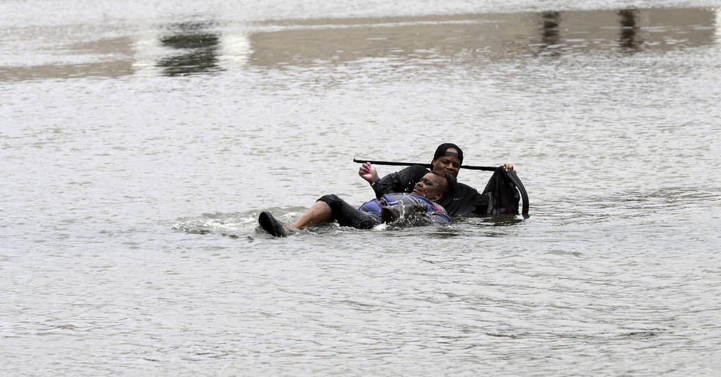 A man helps a woman in floodwaters from Tropical Storm Harvey Sunday, Aug. 27, 2017, in Houston, Texas. The remnants of Hurricane Harvey sent devastating floods pouring into Houston Sunday as risi ...