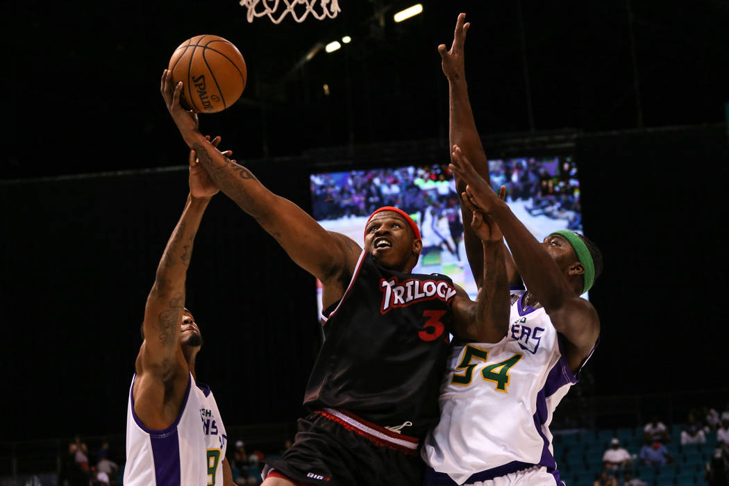 Trilogy's Al Harrington (3) is blocked by 3 Headed Monsters' Rashad Lewis (9) and Kwame Brown (54) during the first half of the Big 3 Championship match at the MGM Grand Garden Arena in Las Vegas  ...
