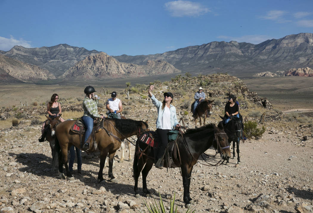 Hayley Miller, center, of Canada takes a selfie as she takes a break with other riders after their horseback riding tour of Red Rock Canyon on Monday, Aug. 28, 2017, in Las Vegas. Bizuayehu Tesfay ...