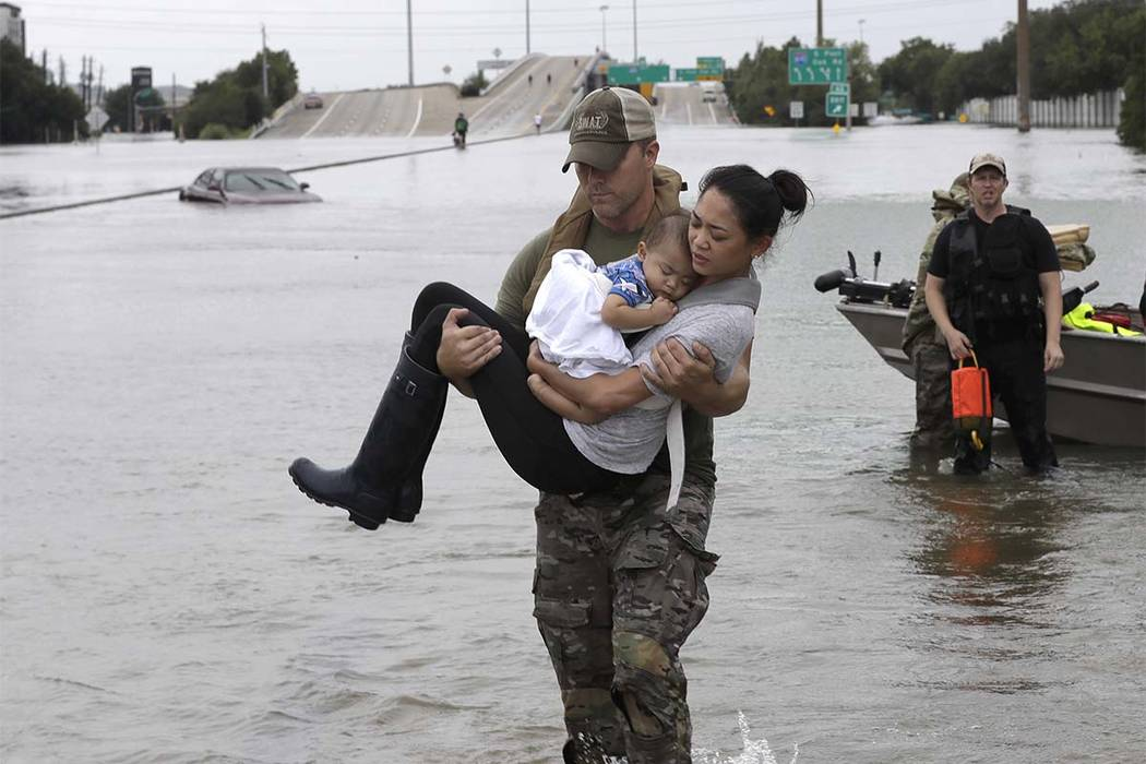 Houston Police SWAT officer Daryl Hudeck carries Catherine Pham and her 13-month-old son Aiden after rescuing them from their home surrounded by floodwater on Sunday, Aug. 27, 2017, in Houston. (D ...