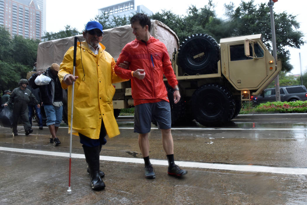 A volunteer walks Enrique Alva, a blind Marine veteran who was evacuated from his home, to the George R. Brown Convention center after Hurricane Harvey inundated the Texas Gulf coast with rain cau ...