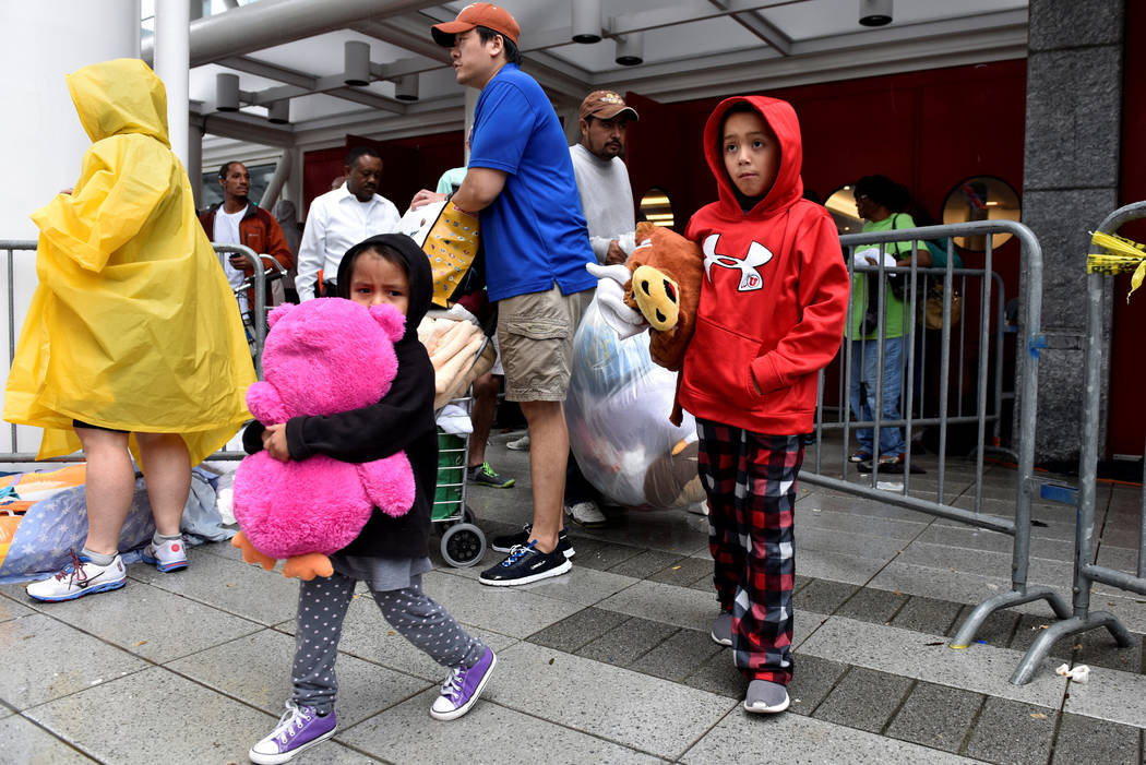 Evacuees carry their belongings outside of the George R. Brown Convention Center where over 9,000 people have taken refuge, in Houston, Texas, U.S. August 29, 2017.  (Nick Oxford/Reuters)