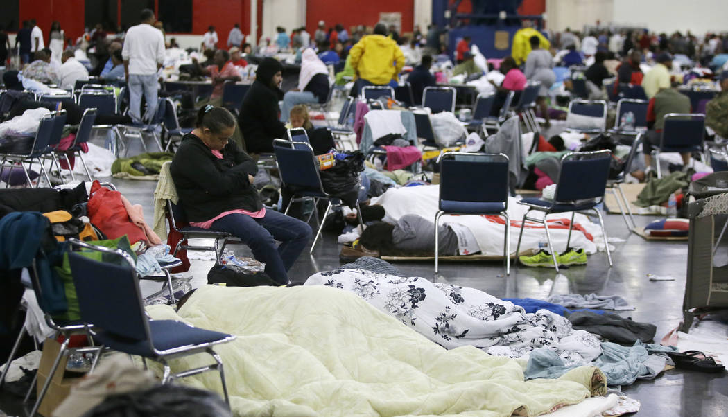 People rest at the George R. Brown Convention Center that has been set up as a shelter for evacuees escaping the floodwaters from Tropical Storm Harvey in Houston on Tuesday, Aug. 29, 2017. (AP Ph ...