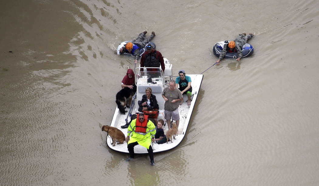 Evacuees make their way though floodwaters near the Addicks Reservoir as floodwaters from Tropical Storm Harvey rise Tuesday, Aug. 29, 2017, in Houston. (David J. Phillip/AP)