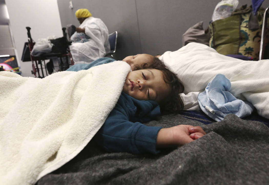 Robert Salgado, 2, sleeps on the floor at the George R. Brown Convention Center that has been set up as a shelter for evacuees escaping the floodwaters from Tropical Storm Harvey in Houston, Texas ...