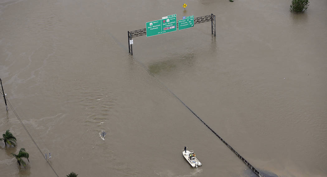 A boat travels along Interstate 10 as floodwaters from Tropical Storm Harvey cover a portion of the highway Tuesday, Aug. 29, 2017, in Houston. (AP Photo/David J. Phillip)