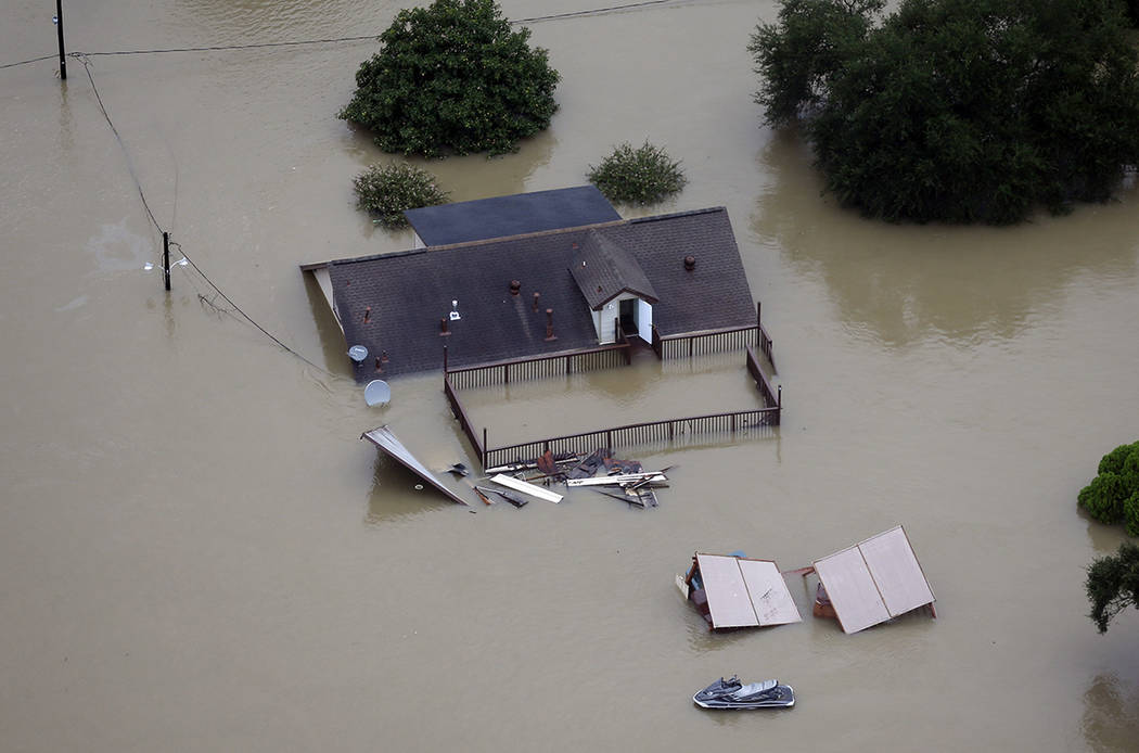 A home is surrounded by floodwaters from Tropical Storm Harvey Tuesday, Aug. 29, 2017, in Houston. (AP Photo/David J. Phillip)