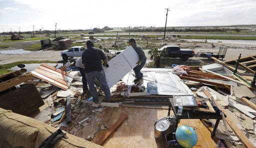 Lupe Tijerina, left, and Andy Guerra, center, and Felix Tijerina, right, work to salvage items from their family home that was destroyed in the wake of Hurricane Harvey, Tuesday, Aug. 29, 2017, in ...