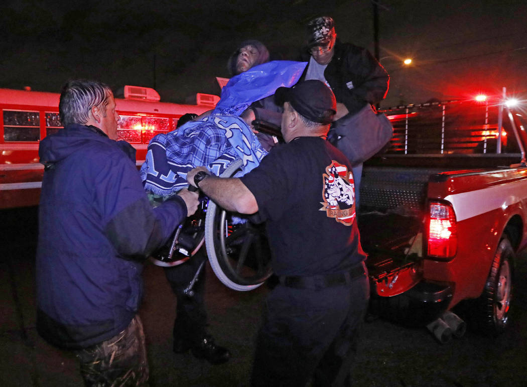 Lake Charles rescue personnel help lower this wheelchair bound resident from the back of a vehicle late Monday night, Aug. 28, 2017, in Lake Charles, Louisiana, after flooding from Harvey's almost ...