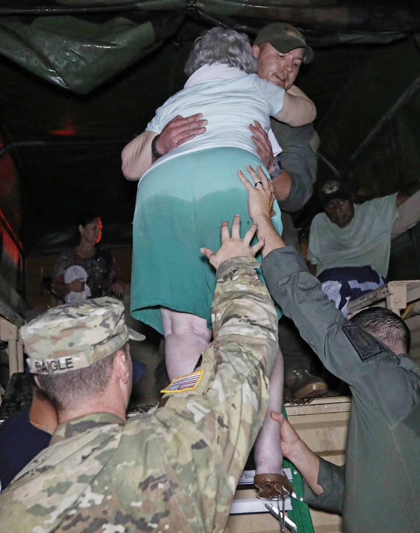 Rescue personnel help lower an elderly woman from the back of a vehicle late Monday night, Aug. 28, 2017, in Lake Charles, Louisiana. (Rogelio V. Solis/AP)