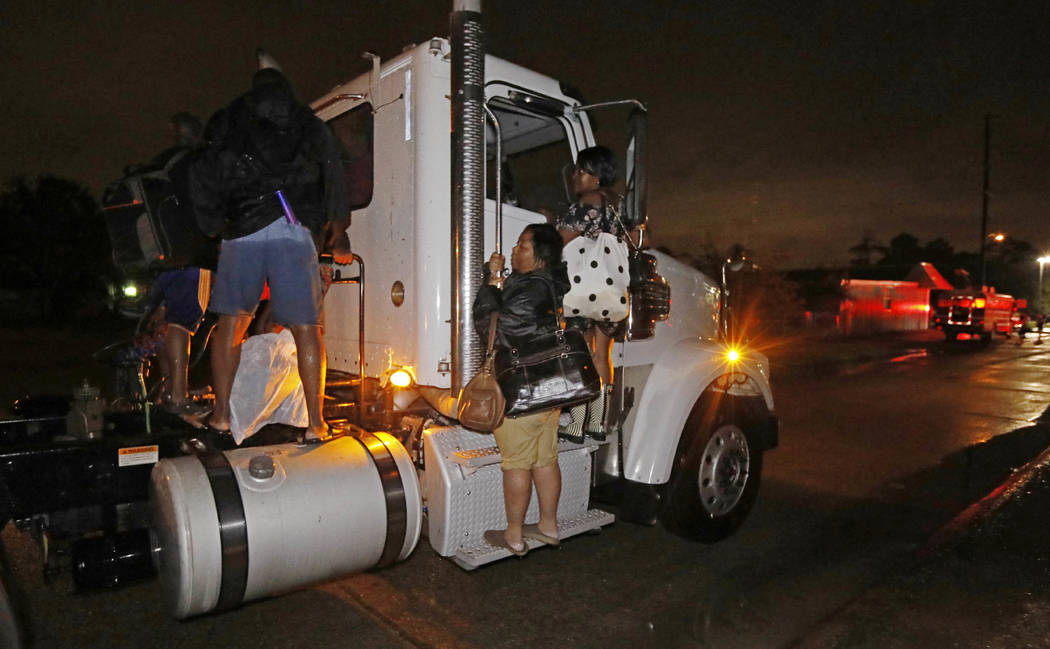 Residents cling to a commercial truck as it carries them to safety following flooding to their homes, late Monday night, Aug. 28, 2017, in Lake Charles, Louisiana. (Rogelio V. Solis/AP)
