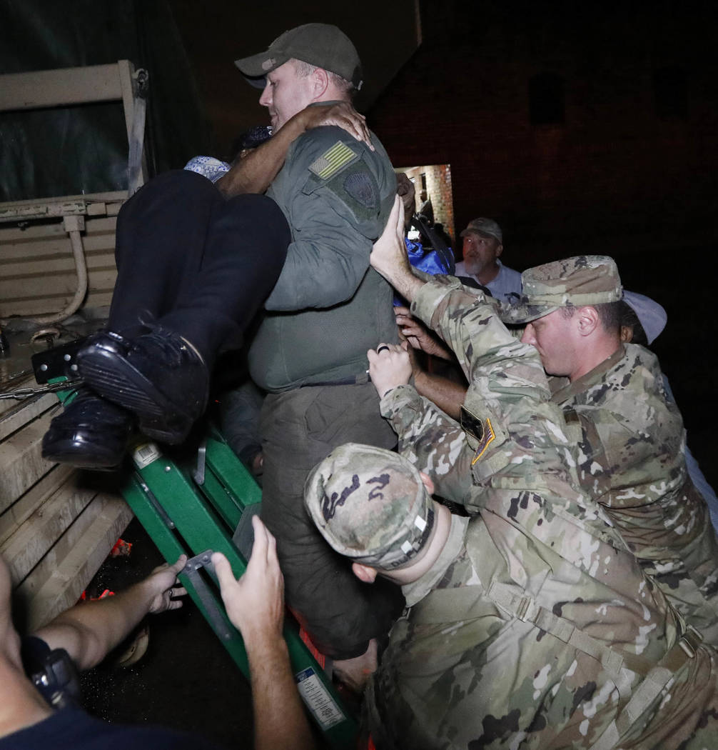 National Guard help brace a rescuer as he lowers a resident from a rescue vehicle late Monday night, Aug. 28, 2017 in Lake Charles, Louisiana. (Rogelio V. Solis/AP)