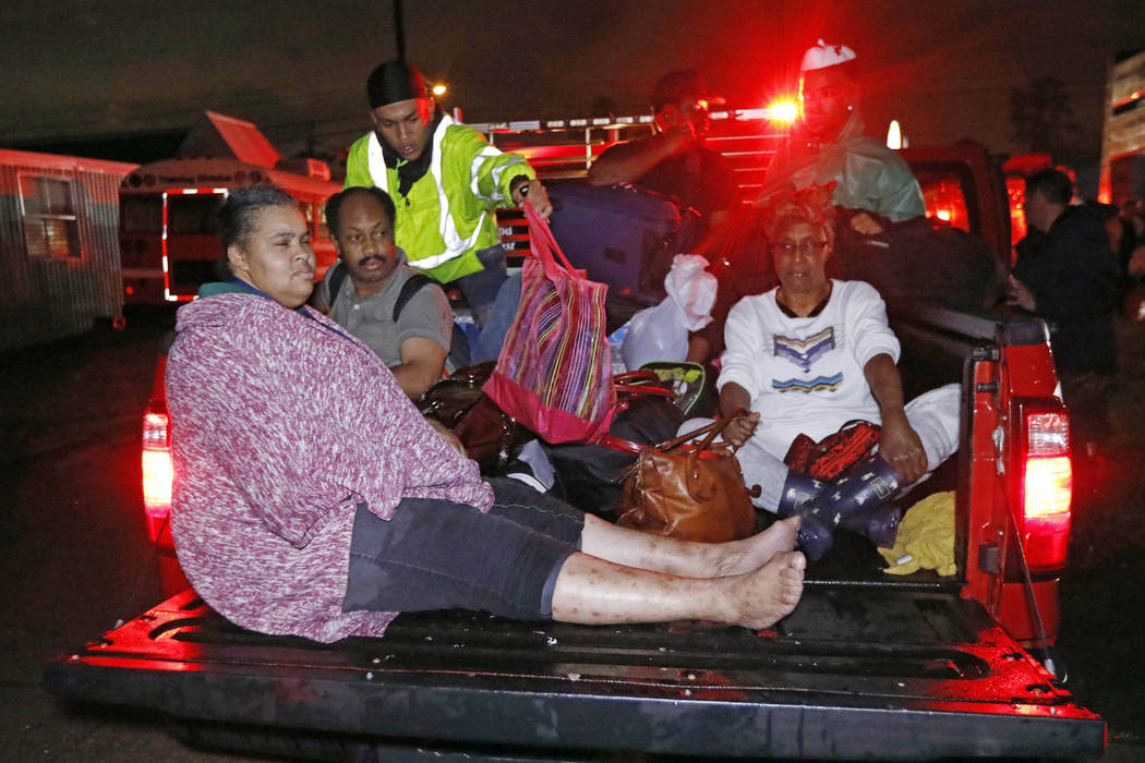 Residents ride in the bed of an emergency vehicle carrying them to safety following flooding to their homes late Monday night, Aug. 28, 2017 in Lake Charles, Louisiana. Almost constant rain over t ...