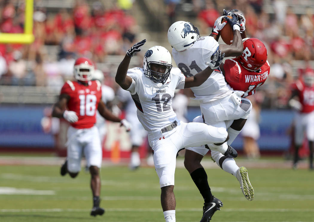 Howard wide receiver JeQuez Ezzard (12) is knocked aside as fellow wide receiver Kyle Anthony (81) tries to keep Rutgers defensive back Isaiah Wharton (11) from making an interception during the f ...