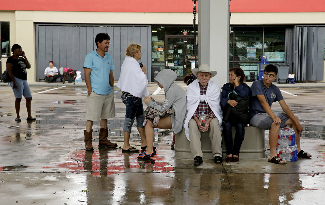 People wait at a staging area for a ride after being evacuated from a neighborhood in west Houston inundated by floodwaters after a release from nearby Addicks Reservoir when it reached capacity d ...