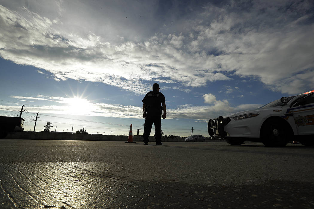 A Harris County Sheriff officer stands at a roadblock along Interstate 45 as rainclouds give way to sunshine after the passing of Tropical Storm Harvey Tuesday, Aug. 29, 2017, in Houston. (AP Phot ...