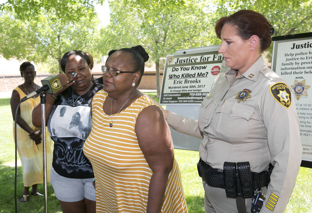 Angela Samuels, left, weeps as her mother, Chris Jackson, also the mother of homicide victim Eric Brooks, holds a briefing with Capt. Roxanne Burke, right, at the community park at the intersectio ...