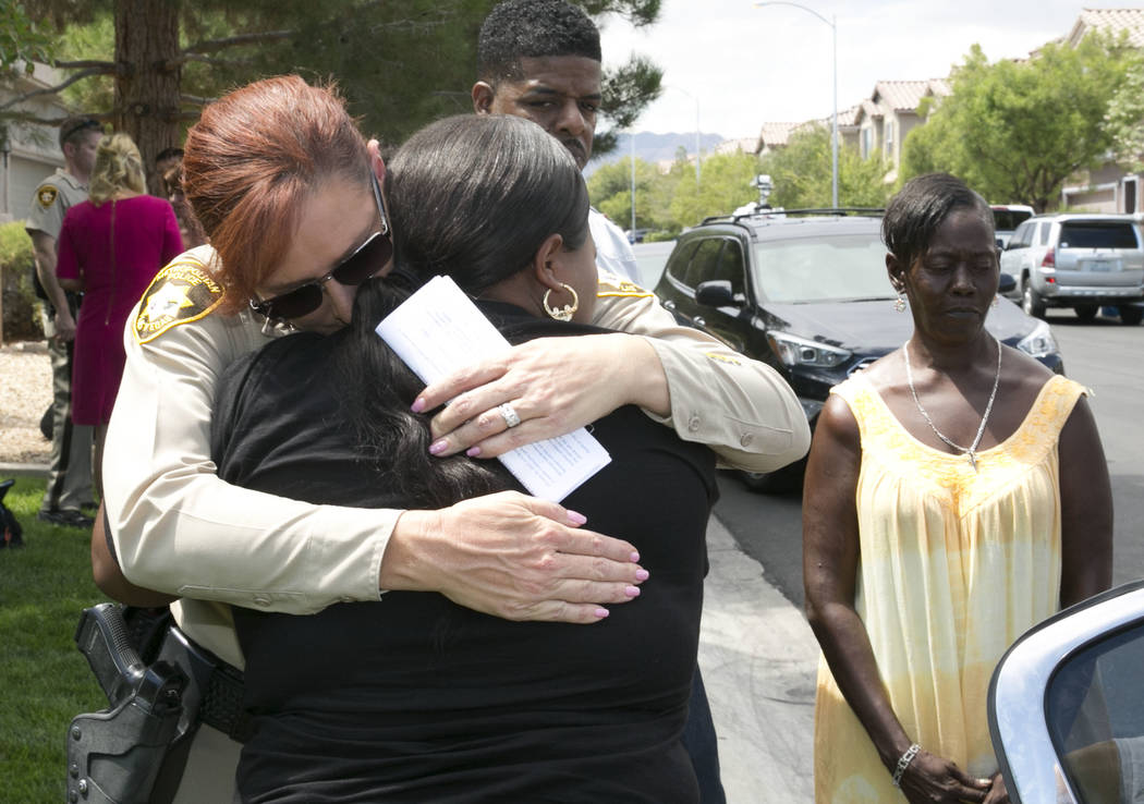 Capt. Roxanne Burke, left, comforts Angela Samuels, sister of homicide victim Eric Brooks, after police and family held a briefing at the community park at the intersection of Seeliger Street and  ...